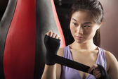 Female boxer wrapper her wrists in the gym — Stock Photo