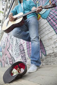 Young street musician playing guitar — Stock Photo