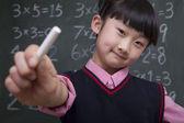 Schoolgirl in front of blackboard holding chalk — Stock Photo