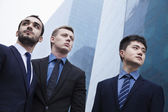Serious businessmen, outdoors, business district — Stock Photo