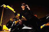 Woman talking on the phone and leaning on her motorcycle at night — Stock Photo