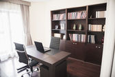 Modern home office with bookshelves — Stock Photo