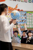 Teacher teaching geography to schoolchildren with a globe — Stock Photo