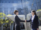Businesswomen shaking hands outdoors — Stock Photo