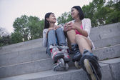 Friends with roller blades — Stock Photo