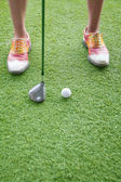 Feet and golf club getting ready to hit a golf ball — Stock Photo