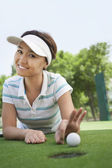 Woman lying down in a golf course — Stock Photo
