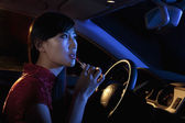 Woman putting on lipstick in the rear view mirror of the car — ストック写真