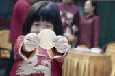 Little girl making dumplings in traditional clothing — Stock Photo