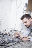 Frustrated man sort computer cables — Stock Photo