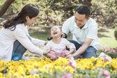 Family sitting in flower garden — Stock Photo