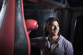 Man at the boxing gym leaning on punching bag — Stock Photo