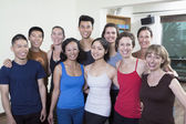 Smiling group of people in a yoga studio — Stock Photo