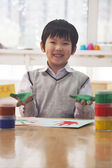 Smiling schoolboy finger painting in art class — Stock Photo