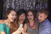 Friends singing together at karaoke — Stock Photo