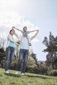 Familia en el parque con hijo sobre los hombros del padre — Foto de Stock