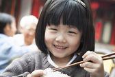 Little girl eating rice — Stock Photo