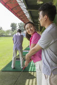 Man teaching his girlfriend how to hit golf balls — Stock Photo