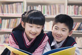 School children reading book a in the library — Stock Photo