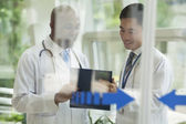 Doctors consulting over medical record — Stock Photo