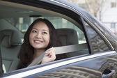 Woman in back seat of car fastening seat belt — Stok fotoğraf