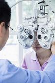 Optometrist doing an eye exam on young woman — Stock Photo