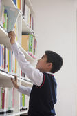 Schoolboy reaching for book off bookshelf — Stock Photo