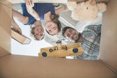 Smiling family looking into a cardboard box — Foto Stock