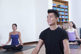 Man sitting cross-legged in a yoga class — Stock Photo