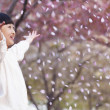 Girl throwing cherry blossom petals — Stock Photo