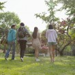 Постер, плакат: Friends walking into a park to have a picnic