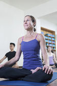Woman sitting cross-legged in a yoga class — Stock Photo
