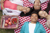 Friends lying on their backs having a picnic — Stock Photo