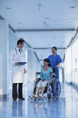 Nurse pushing and assisting patient in a wheelchair — Stock Photo
