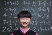 Schoolgirl in front of blackboard with math equations — Stock Photo