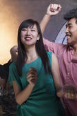 Woman dancing with friends in a nightclub — Stock Photo