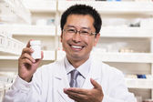 Pharmacist holding a prescription medication bottle — Stock Photo