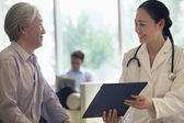 Doctor and patient discussing medical record — Stock Photo