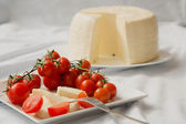 Cherry tomatoes and fresh sicilian cheese — Stock Photo