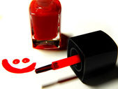 Red nail polish, brush and a smiley face — Stock Photo
