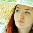 Thoughtful beautiful redheaded woman looking away in a white summer hat outdoors — Stock Photo #40138559