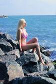 Young beautiful blonde woman in pink bikini smiles — Stock Photo