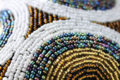 The indian ornament of white, golden, blue and other colorful beads closeup — Stock Photo
