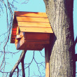 Beautiful wooden birdhouse feeder (nesting box) for birds hanging on a tree — Stock Photo #42290551
