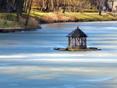 A duck house in the centre of a frozen park lake — Stock Photo