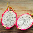 Juicy pink pitaya cut in two pieces on wooden table closeup — Stock Photo