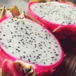 Juicy pink pitaya cut in two pieces on wooden table closeup — Stock Photo #45123951