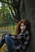 A pretty redhead woman in flannel shirt and jeans sitting under the autumn tree — Stock Photo