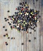 Une collection de poivre noir, rouge, blanc et vert sur la table en bois — Photo