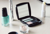 Set of eyeshadow, mascara, primer, turquoise blue nail polish and other cosmetics on a dressing table — Stock Photo
